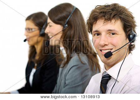 Happy customer service representatives sitting in a row and talking on headset, smiling. Isolated on white background.