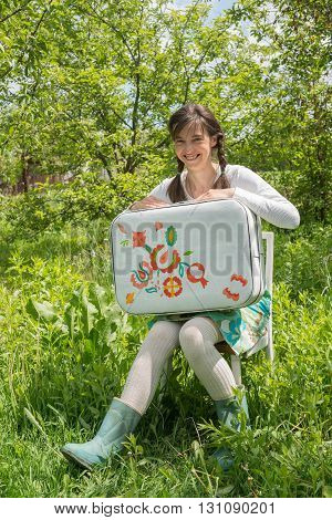 Smiling hipster girl with vintage painted suitcase sits on a wonderful meadow. Concept-before traveling.