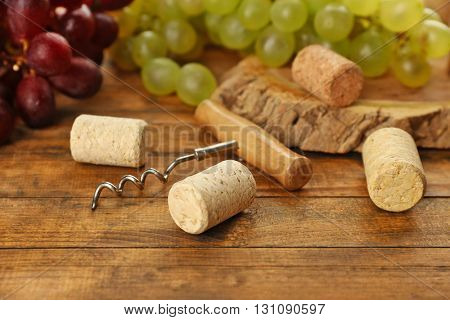 Wine corks and tailspin with grapes on wooden background