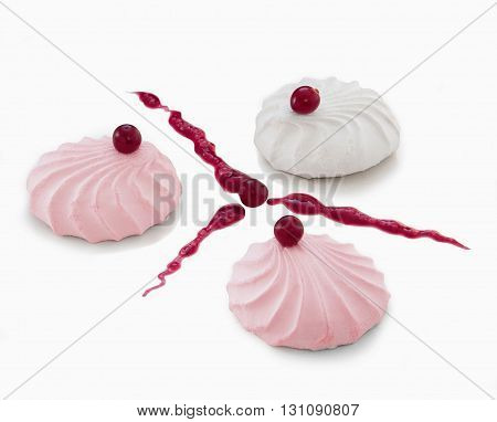 Three marshmallow on a table decorated with cranberries