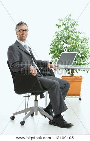 Empresario sittig en el escritorio y trabajar con el ordenador portátil. Mirando a cámara, sonriendo. Aislado en