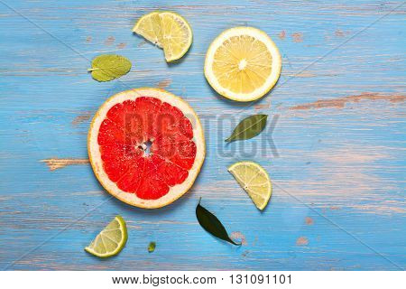 Citrus fruits slices over blue wooden table. Top view. Selective focus