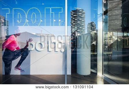 Milan Italy - February 10 2015: Porta Nuova reflections on a shop window of Aulenti square