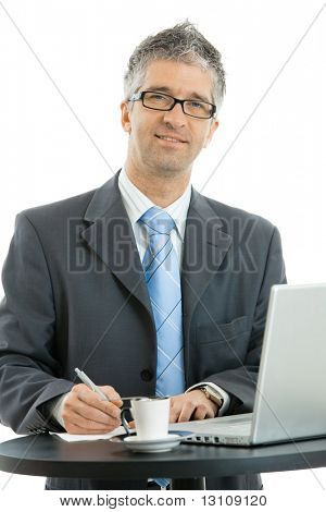 Businessman writing notes on paper standing at coffee table with laptop computer and cup on it. Isolated on white background.