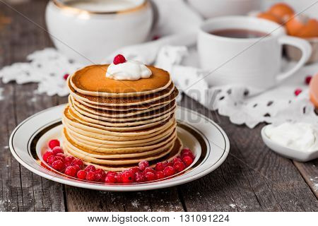 Russian style pancakes with redcurrants and tea on vintage wooden background