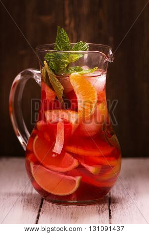 Jar of traditional red spanish sangria drink with different citrus over vintage wooden background. Selective focus