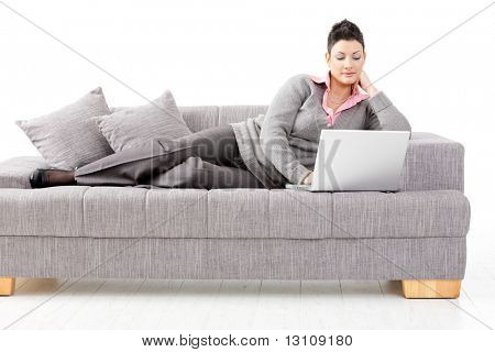 Woman lying on sofa at home working on laptop computer. Isolated on white background.