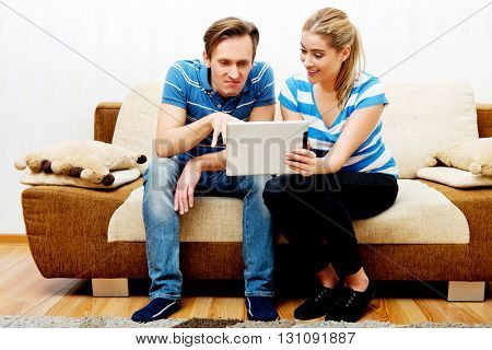 Young couple sitting at home and looking for something on tablet