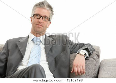 Relaxed businessman sitting on a sofa Isolated on white background.