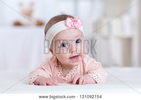 Beautiful baby girl. Smiling kid lying on white bed in nursery room