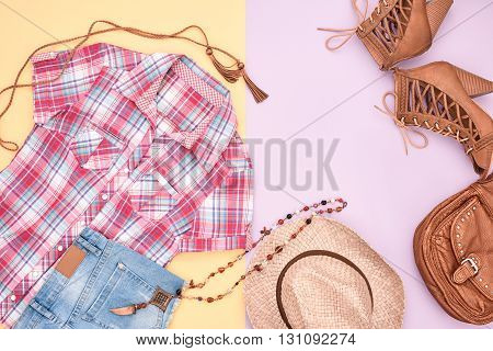 Cowboy street style Fashion girl clothes accessories set. Hipster woman, trendy plaid shirt, denim shorts, shoes, straw hat necklace. Urban country creative outfit. Overhead, top view on pink yellow