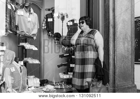 Milan Italy - July 5 2014: A woman while phoning in front of a shopwindow in Corso Vittorio Emanuele