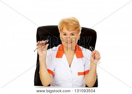 Smile elderly female doctor or nurse sitting behind the desk and holds two pair of glasses