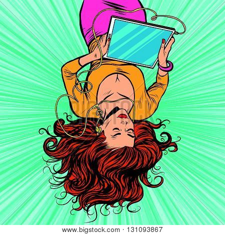 Beautiful upside down girl lies with your graphics tablet with headphones pop art retro vector. Watching movies and Internet. The modern gadgets. New technology, audio and video
