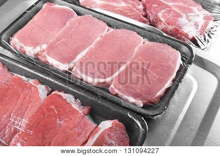 Packed pieces of pork and beef meat on metal background