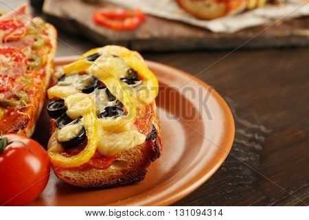 Hot pizza baguette with olives, paprika and salami on wooden table