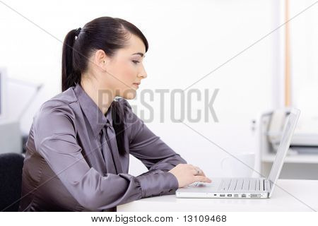 Profile portrait of young businesswoman using laptop computer at office desk, looking at screen.