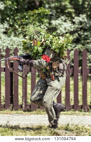 NITRA SLOVAK REPUBLIC - MAY 21: Reconstruction of the Second World War operations between Red and German army camouflaged soldier with a machine gun attacks the enemy on May 21 2016 in Nitra Slovak Republic.
