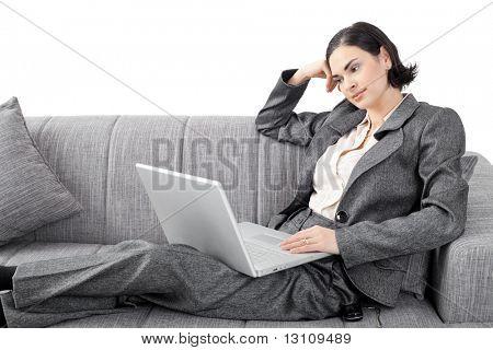 Jovem empresária sentado no sofá, trabalhando com computador portátil. Isolado no fundo branco.