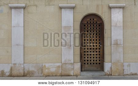 Old wooden doorway, set into a wall, with marble pillars, on the right hand side of the frame