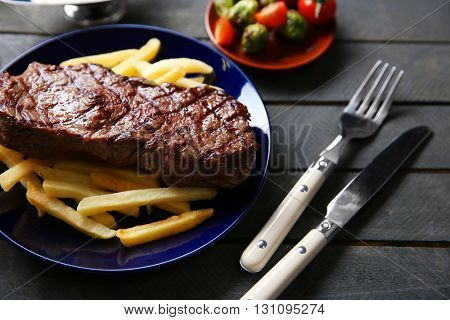 Grilled steak with french fries and vegetables, closeup