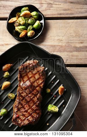Grilled steak with garlic and Brussels sprouts on grill pan, closeup