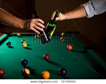 Men clinking beer bottles at snooker table, while playing game.?
