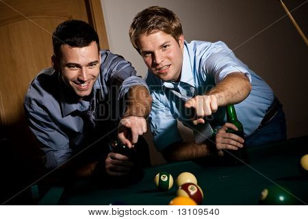Two young men discussing snooker game, having beer, pointing at table.?