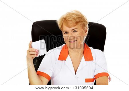 Smile elderly female dentist sitting behind the desk and holds big tooth model