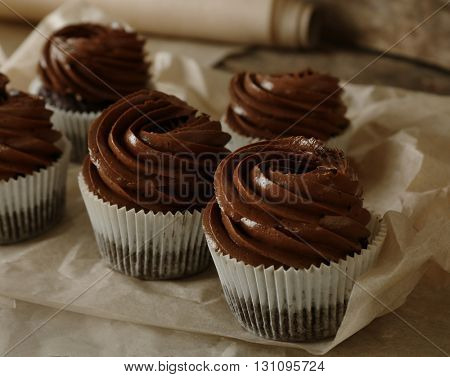Chocolate cupcakes on baker paper over wooden background