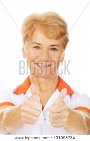 Smile elderly female doctor or nurse shows thumbs up