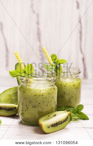 Green refreshing smoothie with kiwi, cucumber and apples over white wooden table. Selective focus