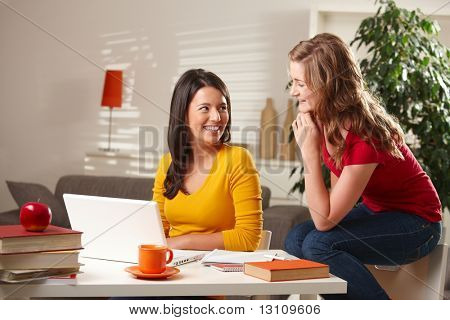 Happy teenage girls laughing together, sitting at table with laptop and books at home.?