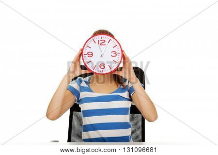 Teenage woman covering her face with a clock
