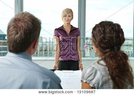 Attractive woman applicant arriving to job interview. Over the shoulder view.