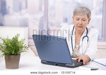 Senior female doctor, working at desk, using laptop computer. Focusing at screen.?
