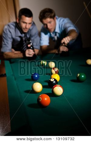 Two young men discussing snooker game at table, having beer, focus on snooker balls.?