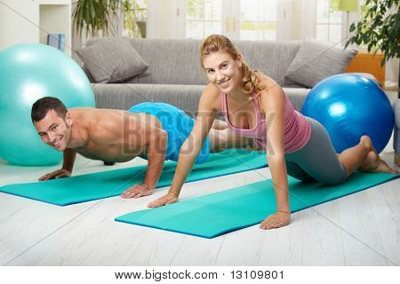 Young couple doing push up exercise at home in living room.