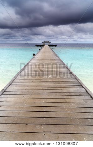 Wooden Jetty Over The Beautiful Maldivian Ocean With Blue Sky