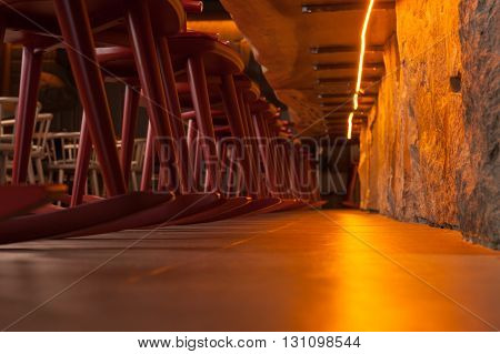 Low angle close-up under the table in restaurant. A row of chair opposite the rocky wall with right