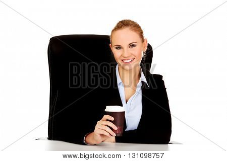 Business woman drinking coffee from paper cup behind the desk