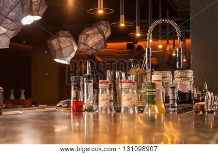 Close up of bar counter with bottles and glasses on it in modern restaurant