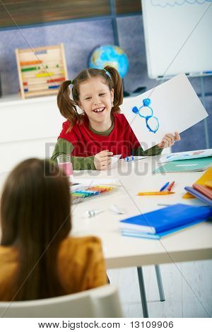 Happy elementary age children enjoying painting with colors in art class at primary school classroom, smiling, laughing.?
