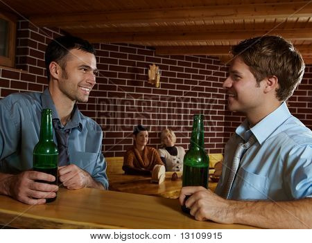 Smiling young men sitting at bar in pub drinking beer, women sitting in background.?