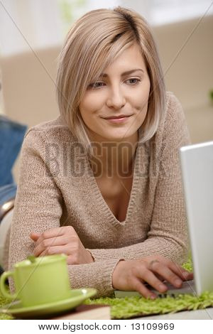 Portrait of attractive young blonde woman lying on floor at home looking at laptop, smiling.?