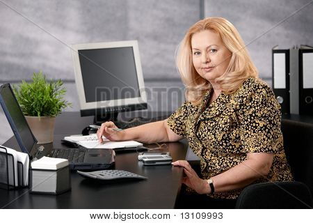 Senior woman sitting at office desk working, looking at camera smiling.?