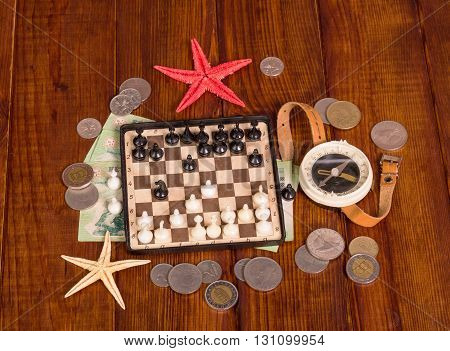 Accessories for the traveler: chess, compass, money and starfish on a background of dark wood.