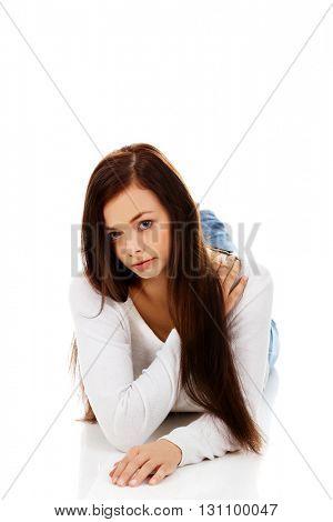Young sad woman lies on the floor