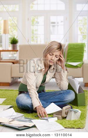 Unruhigen Woman sitting on Floor mit überquerte Beine, Berechnung im Wohnzimmer tun.?