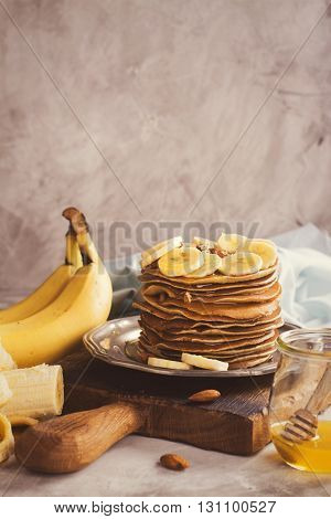 Stack of pancakes with banana, nuts and honey over stone background. Toned image. Selective focus. Space for text